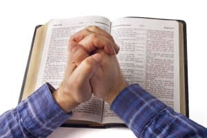 Praying hands over open bible